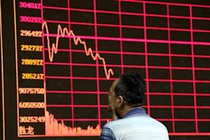 An investor looks at an electronic board showing stock information of Shanghai Stock Exchange Composite Index in Beijing