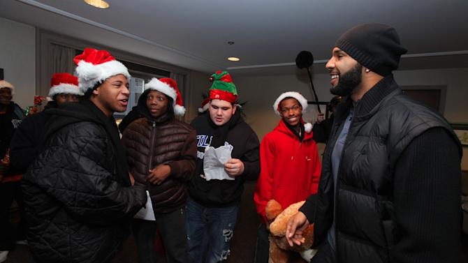 Chicago running back Matt Forte leads the Tilden High School football team with Toys for Tots through caroling rehearsals before completing random acts of kindness in downtown Chicago for the Duracell Power Holiday Smiles program on December 17, 2012, in Chicago. (Photo by Barry Brecheisen/Invision/AP)
