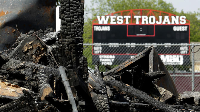 Five days after a fertilizer plant explosion, a score board at the school football stadium is seen in the distance beyond a burned-out house Monday, April 22, 2013, in West, Texas. The massive explosion at the West Fertilizer Co. last Wednesday killed 14 people and injured more than 160 others. (AP Photo/Charlie Riedel)