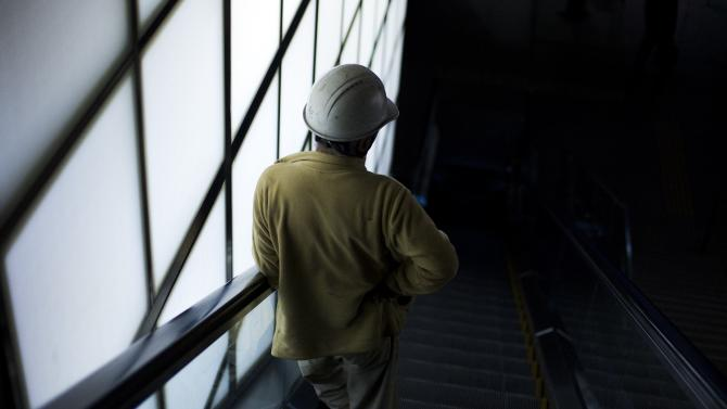 Construction worker descends on an escalator at a subway station in a banking district in central Tokyo