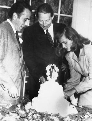 FILE - In this May 21, 1945 file photo, novelist Louis Bromfield, center, helps actor Humphrey Bogart and his bride, actress Lauren Bacall, cut the cake after their wedding at Bromfield's Malabar Farm near Lucas, Ohio. The couple's oldest child, Stephen Bogart, is helping to raise money to renovate part of Malabar Farm, which is now part of a state park. (AP Photo/File)