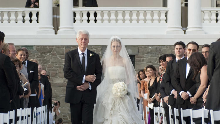 "FILE - This July 31, 2010 file photo released by Genevieve de Manio Photography shows former President Bill Clinton walking his daughter Chelsea down the isle for her wedding in Rhinebeck,N.Y. No one, including Clinton and designer Wang, expected the media circus that accompanied last year's wedding, says Darcy Miller, editor in chief of Martha Stewart Weddings, but all those photos and attention meant that a lot of gowns are coming out now that were inspired by the delicate strapless with a jeweled waistband. ""It was copied in the industry immediately. It's the classic, romantic, fairy-tale dress on a modern woman.""     (AP Photo/Genevieve de Manio Photography,Genevieve de Manio, File) NO SALES; EDITORIAL USE ONLY"