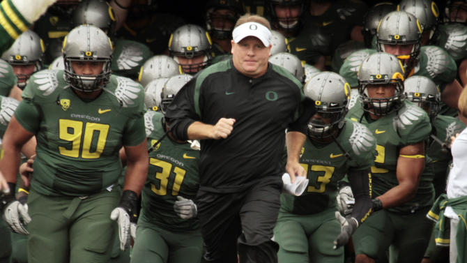 FILE - In this Sept. 17, 2011 file photo, Oregon head football coach Chip Kelly leads the team onto the field for an NCAA college football game against Missouri State in Eugene, Ore. The NCAA has taken away a scholarship and placed Oregon's football program on probation for three years for recruiting violations under previous coach Chip Kelly. The NCAA's Division I Infractions Committee released a report on Wednesday, June 26, 2013, that found Kelly and the university failed to monitor the program.(AP Photo/Don Ryan, File)