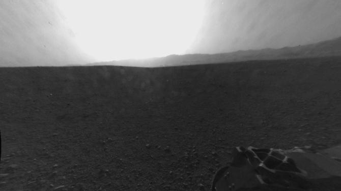 """This photo provided by NASA shows a full-resolution version of one of the first images taken by a rear Hazard-Avoidance camera on NASA's Curiosity rover, which landed on Mars the Sunday evening, Aug. 5, 2012. The image was originally taken through a """"fisheye"""" wide-angle lens, but has been """"linearized"""" so that the horizon looks flat rather than curved. A Hazard-avoidance camera on the rear-left side of Curiosity obtained this image. Part of the rim of Gale Crater, which is a feature the size of Connecticut and Rhode Island combined, stretches from the top middle to the top right of the image. One of the rover's wheels can be seen at bottom right. (AP Photo/NASA/JPL-Caltech)"""