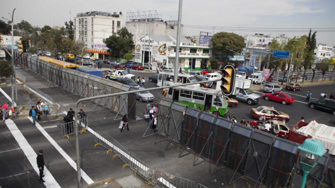 The street where Mexico's Congress is located is shown blocked by a metal barricade in Mexico City, Monday, Nov. 26, 2012. Police heightened security around the building where Mexico's President-elect Enrique Pena Nieto, of the Institutional Revolutionary Party (PRI) will be sworn-in on Dec. 1. (AP Photo/Eduardo Verdugo)