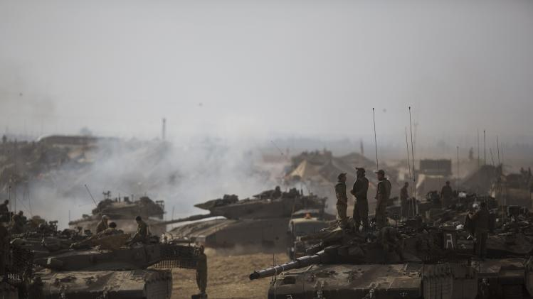 Israeli soldiers stand atop a tank at a staging area, near the border with the Gaza Strip