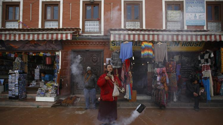 A monk swings an incense burner while offering daily prayers at the premise of Boudhanath Stupa in Kathmandu