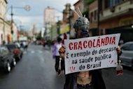 "A demonstrator holds a banner reading ""Cracolandia is an example of the failure of Brazilian public health policy"" during a demonstration against paramilitary police's clean-up operation in the area called ""Cracolandia"" (Crackland) in downtown Sao Paulo, Brazil on January 14"