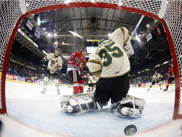 Portland Winterhawks' Leipsic watches the puck go past London Knights' Patterson with Knights' Harrington on Winterhawks' Rattie's goal during the Memorial Cup Canadian Junior Hockey Championships in