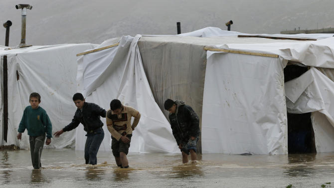 Syrian refugee boys make their way in flooded water at a temporary refugee camp, in the eastern Lebanese Town of Al-Faour near the border with Syria, Lebanon, Tuesday, Jan. 8, 2013. Two Syrian refugee encampments in Lebanon's eastern Bekaa valley were completely immersed in water Tuesday after the Litani river flooded and the water came pouring into their tents. The flood forced dozens of Syrian refugees to leave in search for alternative shelter along with their water-soaked and muddied belongings. (AP Photo/Hussein Malla)