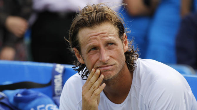 Argentina's David Nalbandian looks on as he wait for the trophy presentation after he was disqualified for causing an injury to the line judge during the Queen's Club grass court championships final tennis match against Croatia's Marin Cilic, London, Sunday, June 17, 2012. (AP Photo/Sang Tan)