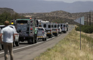 A procession of the vehicles left by the 19 elite Granite Mountain Hotshot crew members killed over the weekend are removed from the fire area near Yarnell, Ariz., Wednesday, July 3, 2013. Violent wind gusts on Sunday turned a small, lightning-ignited forest fire in the town into an out-of-control wildfire that left no escape for the team of Hotshots. (AP Photo/Chris Carlson)