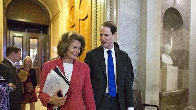 Sen. Lisa Murkowski, R-Alaska, left, and Sen. Ron Wyden, D-Ore., right, leave the Senate floor after voting on legislation to collect sales tax on Internet purchases, on Capitol Hill in Washington, Monday, May 6, 2013.  (AP Photo/J. Scott Applewhite)