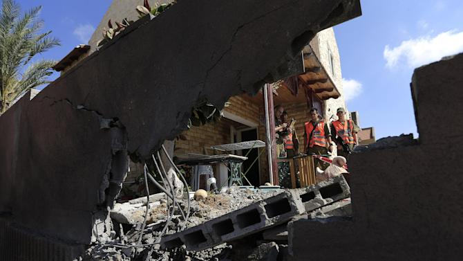 """Israeli soldiers stand at a damaged home after a rocket fired by Palestinian militants in Gaza, landed in the southern town of Sderot Thursday, July 3,2014. Israeli military carried out airstrikes on the Gaza Strip after Palestinian militants fired rockets into Israel early Thursday. The Israeli military said the air force struck 15 """"terror sites"""" in Gaza. """"The targets included weapons manufacturing sites as well as training facilities,"""" a military spokesman said. (AP Photo / Tsafrir Abayov)"""