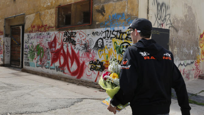 """Mouad Belghouat known as el-Haqed or """"the Enraged,"""" walks with flowers received from activists after a press conference at the old slaughterhouse in Casablanca, Friday March 29, 2013. The Moroccan rapper, known for his social activism and protest songs, said he will concentrate on his music and studies after being released from prison for insulting police. (AP Photo/Abdeljalil Bounhar)"""
