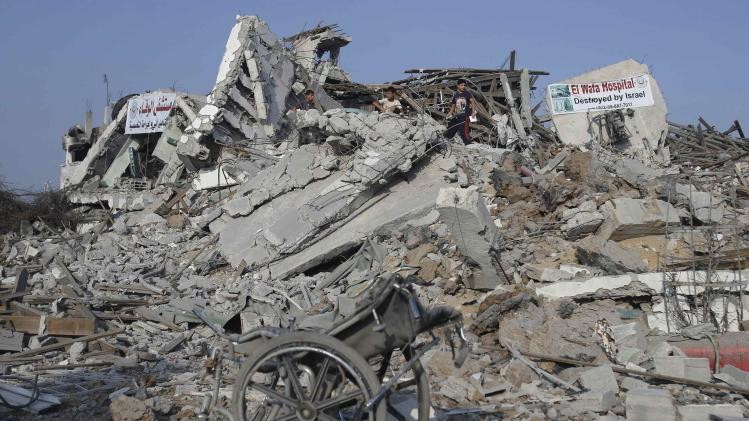 Wheelchair is seen as Palestinians stand atop the ruins of the headquarters of El-Wafa rehabilitation hospital, which witnesses said was destroyed during a seven-week Israeli offensive, in the east of Gaza City