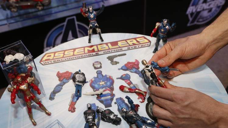 Toy demonstrator Clayton Morris uses the interchangeable parts of Hasbro's IRON MAN 3 IRON ASSEMBLERS figures to create custom armors in the company's showroom at the American International Toy Fair, Friday, Feb. 8, 2013, in New York. (Photo by Jason DeCrow/Invision for Hasbro/AP Images)