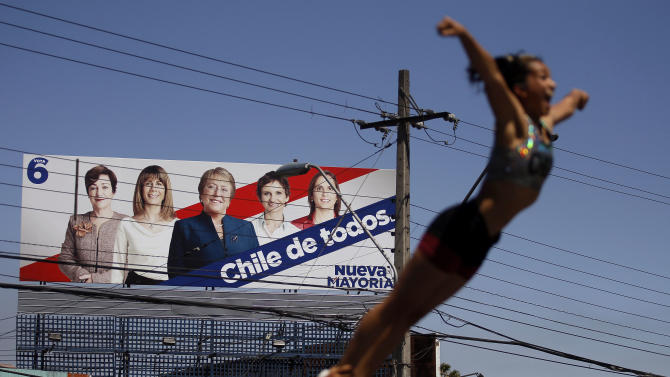 An election campaign sign for former President Michelle Bachelet stands along a road where a street performer does her act in Santiago, Chile, Saturday, Nov. 16, 2013. Bachelet is running for reelection in Chile's general elections on Sunday. (AP Photo/Luis Hidalgo)