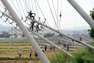 Workers repair a row of fallen electric poles in Wenling, east China's Zhejiang province. A typhoon slammed into eastern China on Wednesday, the country's third in a week, killing at least three people and causing more than $1.5 billion in damage, state media said