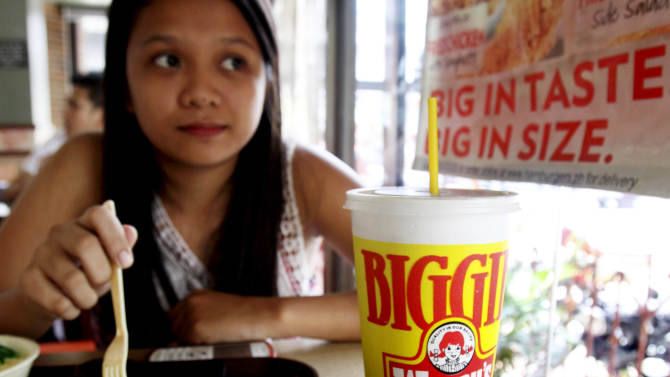 """Pearl Ganotisi sips from her 24-ounce of soda drinks as she takes her meal in an American hamburger chain Friday, June 1, 2012 in Manila, Philippines.   New York Mayor Michael Bloomberg has proposed a ban on the sale of large sodas and other sugary drinks in restaurants, delis and movie theaters in the hopes of combating obesity. Under his plan, sugary drinks would be limited to 16 fluid ounces _ almost half a liter. Around the world, portion sizes are generally smaller. Perceptions of American overconsumption have been fueled by films such as """"Super Size Me"""" and the spread of U.S. fast-food chains. (AP Photo/Pat Roque)"""