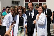 French President Francois Hollande (C) speaks with nurses on August 11 after a visit to the hospital in Grenoble where an injured jeweler was hospitalized after a holdup. Hollande will celebrate 100 days since his election as French president on Tuesday knowing his honeymoon with the electorate is over and that life is not going to get easier any time soon