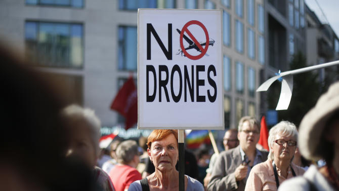 A woman holds a poster against drones during a demonstration against the upcoming visit of United States President Barack Obama in Berlin, Monday, June 17, 2013. President Obama will visit the German capital on Tuesday, June 18, and Wednesday June 19, 2013. (AP Photo/Markus Schreiber)