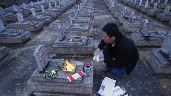 Thiem Nguyen burns incense in front of a tomb of an unknown soldier at the Viet-Laos cemetery in the border district of Anh Son