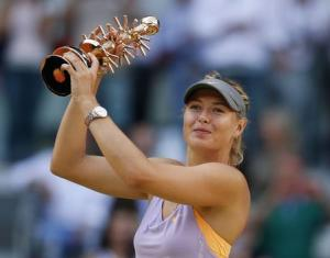 Maria Sharapova of Russia celebrates holding the Ion Tiriac trophy after winning the Madrid Open final tennis match over Simona Halep of Romania in Madrid