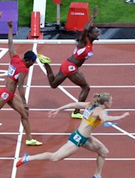 Australia's Sally Pearson (bottom), USA's Kellie Wells and USA's Dawn Harper (top) cross the finish line of the women's 100m hurdles final at the athletics event during the London 2012 Olympic Games in London