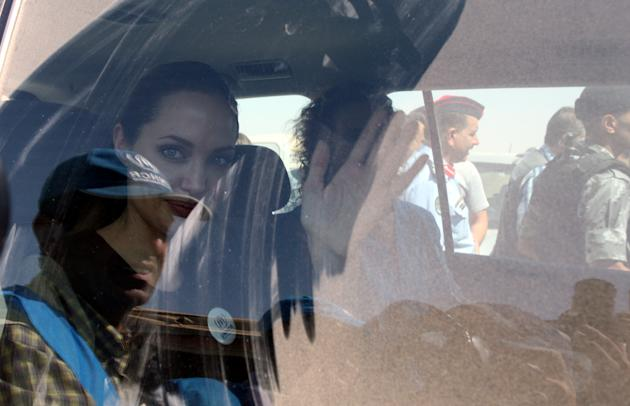 The U.N. refugee agency's special envoy, actress Angelina Jolie, waves through the dusty window of her car as she departs the Zaatari Refugees Camp in Jordan for Syrians who fled the civil war in thei