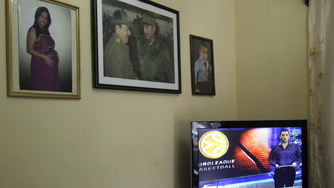 In this Feb. 1, 2013 photo, pictures of Cuban leader Fidel Castro and Cuba's President Raul Castro hang on the wall of a home as a television shows the Venezuelan channel Telesur in Havana, Cuba. Telesur, which is bankrolled primarily by Venezuela, has been broadcast live about 12 hours a day on the island's open airwaves since Jan. 20. Telesur's outlook may be sympathetic to Cuba's socialist model, but it's still a relatively unfiltered news source, and many say the decision to carry it here is as groundbreaking as other recent reforms, such as legalizing more private businesses or allowing greater travel freedom. Telesur was conceived as a force for regional integration and as a counterweight to Western channels such as CNN and the BBC. (AP Photo/Ismael Francisco, Cubadebate)