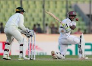 Shivnarine Chanderpaul plays a shot as Mushfiqur Rahim watches in Dhaka on Tuesday. Chanderpaul and opener Kieran Powell hit stubborn hundreds to give the West Indies a commanding start in the first Test