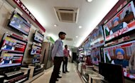 Bystanders watch television screens with Indian Prime Minister Manmohan Singh as he addresses the nation in New Delhi. India&#39;s Prime Minister Manmohan Singh mounted a defiant defence Friday of reforms that resulted in the loss of his government&#39;s majority, saying he had to act to bolster growth and restore confidence