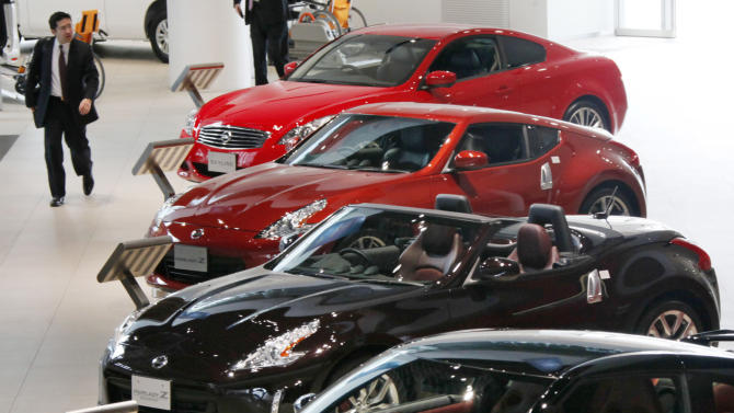 A visitor inspects Nissan sports cars at a gallery inside the headquarters of Nissan Motor Co. in Yokohama, Japan, Friday, Feb. 8, 2013. The Japanese auto maker suffered a 34.6 percent plunge in October-December profit to 54.1 billion yen (US$579 million) as global sales languished, especially in China, where anti-Japanese sentiment flared over a territorial dispute. (AP Photo/Koji Sasahara)