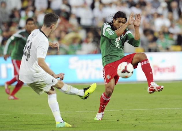 Mexico's Carlos Pena, right, defends himself from New Zealand's Storm Roux during their World Cup qualifying soccer match at Westpac Stadium, in Wellington, New Zealand, Wednesday, Nov. 20, 2013. Mexi
