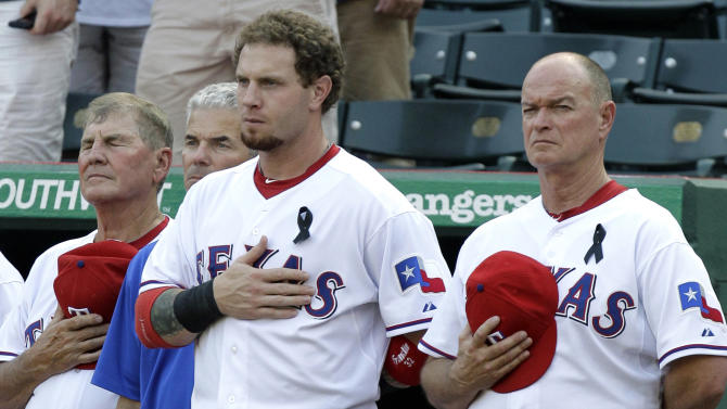 Texas Rangers' Jackie Moore, from left, athletic trainer Jamie Reed, Josh Hamilton and coach Johnny Narron, right, stand during a moment of silence before the start of a baseball game against the Oakland Athletics, Friday, July 8, 2011, in Arlington, Texas. A fan, Shannon Stone, fell trying to catch a baseball tossed to him by Hamilton at Thursday's game between the two teams. Stone died later at a hospital. (AP Photo/Tony Gutierrez)