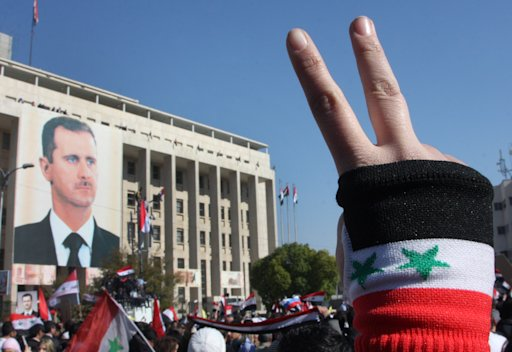 A pro-Syrian regime protester flashes V-victory sign during a protest against the Arab League sanctions, in Damascus, Syria, on Monday Nov. 28, 2011.  Syria's economy minister called newly approved Arab League sanctions 