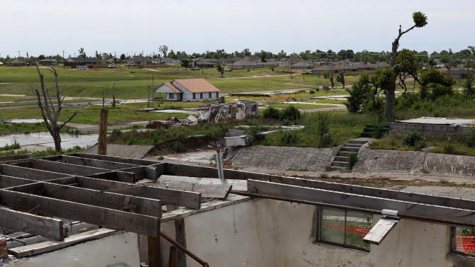 In this photo taken Tuesday, May 8, 2012, a new home rises among ruins of others in a Joplin, Mo., neighborhood which was destroyed by an EF-5 tornado nearly a year ago. Reconstruction continues in the community as the anniversary of the costliest tornado on record approaches on May, 22. (AP Photo/Charlie Riedel)