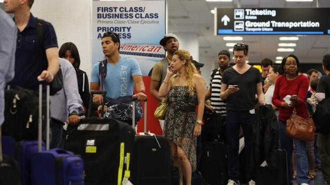 American Airlines passengers wait in line for a flight at Miami International Airport on April 16.