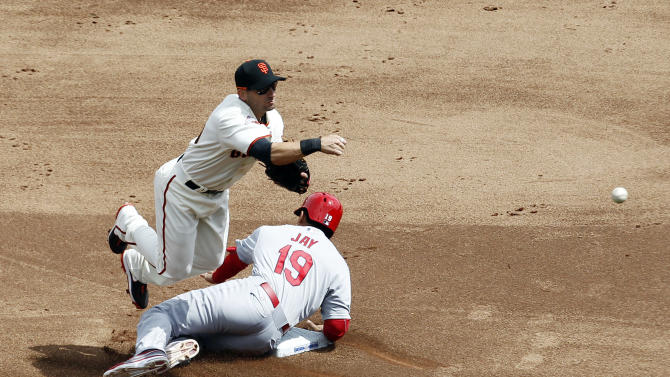 San Francisco Giants second baseman Marco Scutaro, top, turns a double play over St. Louis Cardinals' Jon Jay  (19) on a ground ball from Carlos Beltran during the third inning of a baseball game on Friday, April 5, 2013, in San Francisco. (AP Photo/Tony Avelar)