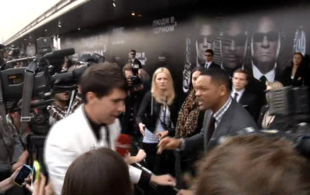 In this video image taken from AP video U.S. actor Will Smith, center right, reacts after he was embraced by reporter Vitalii Sediuk, white suit, from the Ukrainian television channel 1+1  on the red