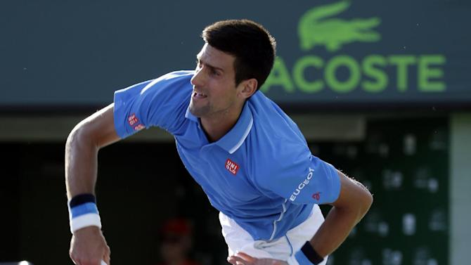 Novak Djokovic, of Serbia, follows through on a serve to Steve Darcis at the Miami Open tennis tournament, Monday, March 30, 2015, in Key Biscayne, Fla. (AP Photo/Lynne Sladky)