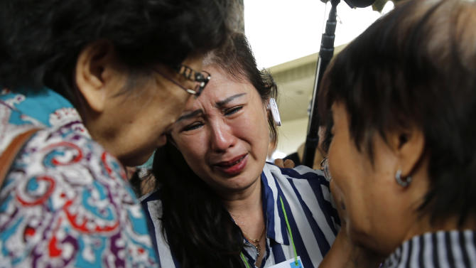 Relatives of passengers onboard AirAsia flight QZ8501 cry in a waiting area at Juanda International Airport in Surabaya
