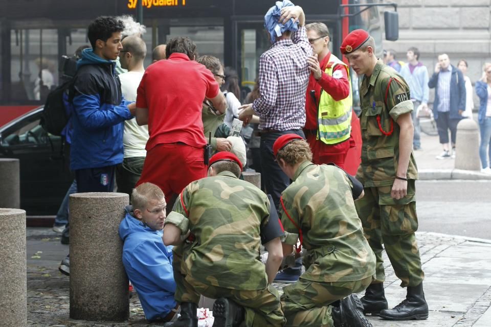 Wounded people are treated in the street in the centre of Oslo, Friday July 22, 2011, following an explosion that tore open several buildings including the prime minister's office, shattering windows and covering the street with documents and debris. (AP Photo/Scanpix, Berit Roald)