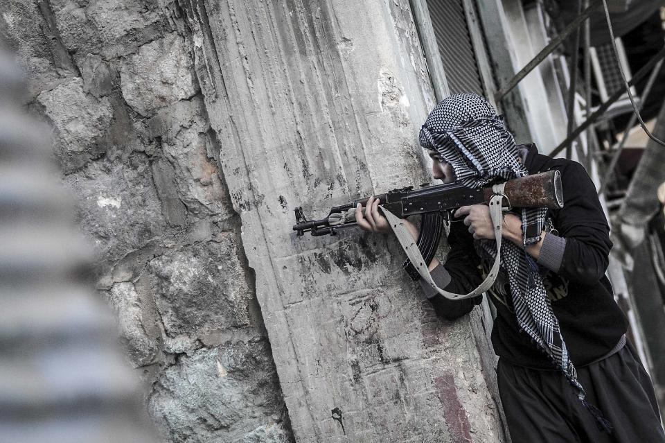 In this Saturday, Oct. 27, 2012 photo, a rebel fighter keeps an eye over an enemy position as he moves through the frontline, in the southeast area of Aleppo, Syria. (AP Photo/Narciso Contreras).