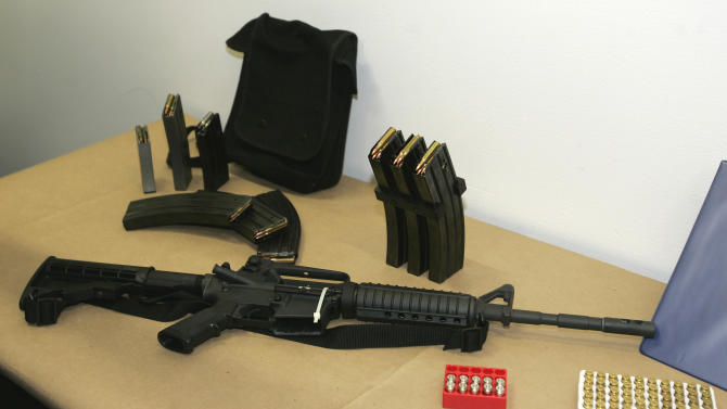FILE - In this March 27, 2006 file photo, a Bushmaster AR-15 semi-automatic rifle and ammunition is seen at the Seattle Police headquarters in Seattle. In an effort to stem the illicit flow of weapons into Mexico, the Justice Department says gun shops in four Southwest border states will be required to alert the federal government to frequent buyers of high-powered rifles. (AP Photo/Ted S. Warren, File)