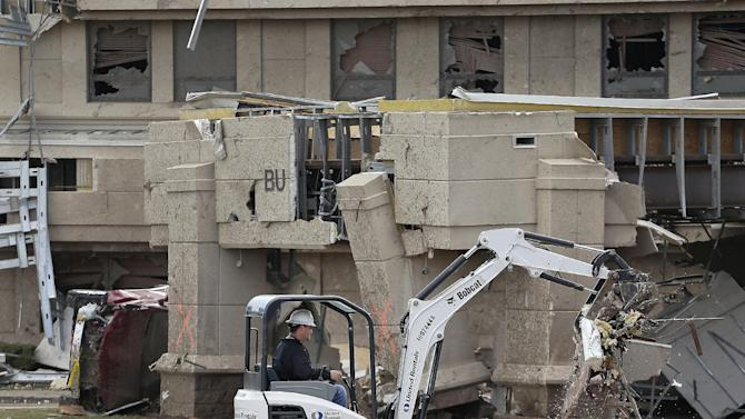A worker removes clears debris from the tornado-ravaged Moore Medical Center Wednesday, May 22, 2013, in Moore, Okla. Cleanup continues two days after a huge tornado roared through the Oklahoma City suburb, flattening a wide swath of homes and businesses. (AP Photo/Charlie Riedel)