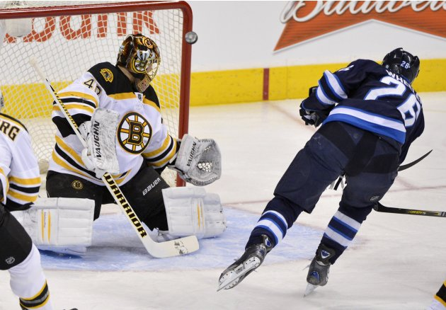 Bruins goaltender Rask makes a save on Jets' Wheeler during the first period of their NHL hockey game in Winnipeg