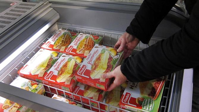 FILE - In this Feb. 11, 2013 file photo, a customer takes a pack of frozen beef Hachis Parmentier from a freezer in a supermarket in Nice, southeastern France. The Europe-wide uproar over fraudulently labeled horse meat, sold as beef, has exposed the labyrinthine path of companies and countries across the continent that meat for prepared dishes takes before it reaches that microwave. But the back story reveals a France as dependent on factory food as other nations, and a people increasingly torn between their heritage and their hectic lives. (AP Photo/Lionel Cironneau, File)