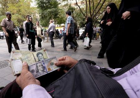 Money changer displays U.S. and Iranian banknotes at the Grand Bazaar in central Tehran